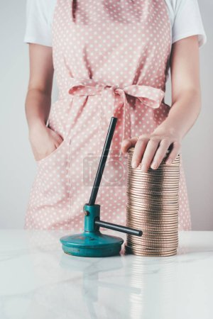 cropped image of woman in apron touching jar lids at kitchen