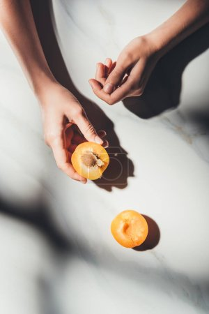 Photo for Partial view of woman holding piece of apricot on light marble surface - Royalty Free Image