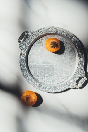 top view of pieces of ripe apricot on metal tray and light marble tabletop