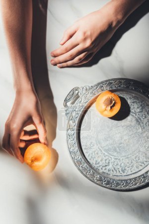 partial view of woman holding piece of apricot on light marble surface