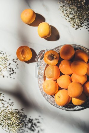flat lay with ripe apricots on metal tray with gypsophila flowers on light marble tabletop with shadows
