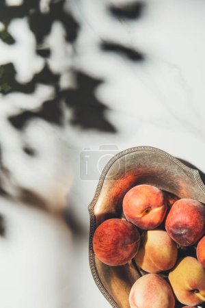flat lay with ripe peaches in metal bowl on light marble surface with shadows
