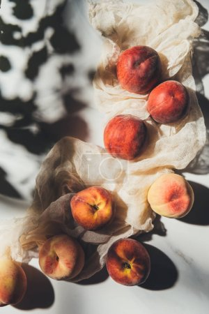 flat lay with ripe peaches and gauze on light marble tabletop with shadows