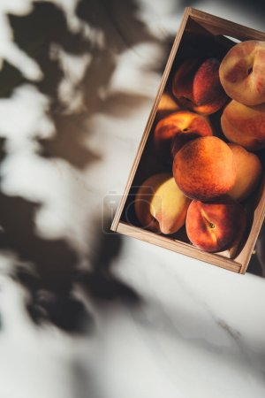 top view of wooden box full of fresh peaches on light marble surface with shadows