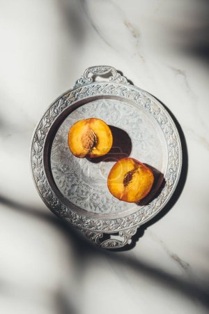 top view of pieces of peach on metal tray on light marble tabletop with shadows