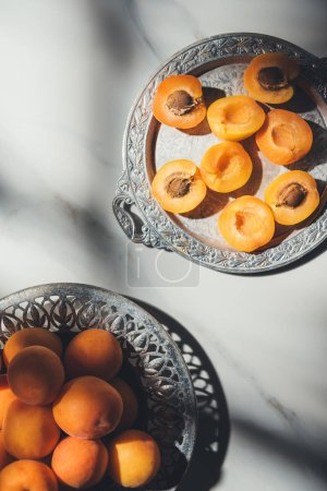 flat lay with fresh apricots in metal bowl and on tray on light marble surface with shadows