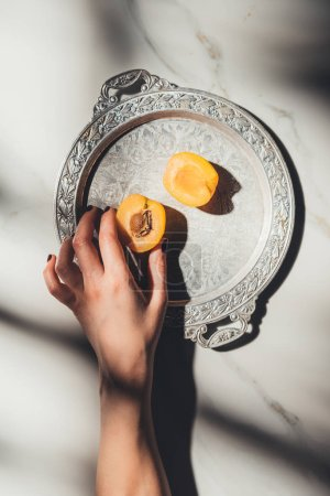 Cropped shot of woman holding apricot piece on metal tray on light marble surface
