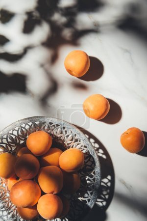 flat lay with ripe apricots in metal bowl on light marble surface with shadows