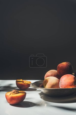 food composition with ripe peaches in metal bowl on black backdrop