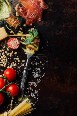 Photo for View from above fork wrapped by pasta surrounded by pine nuts, pesto, parmesan, raw spaghetti, cherry tomatoes, salt, olive oil and jamon on table - Royalty Free Image