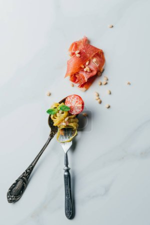 elevated view of spoon and fork wrapped by pasta with mint leaves, pine nuts, jamon and cherry tomatoes covered by grated parmesan on marble table