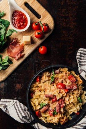 Foto de Vista superior de pasta con jamón, piñones, salsa, tomates cherry, hojas de menta cubierto de queso parmesano rallado en cazuela rodeada de toallas de cocina y tabla para cortar con los ingredientes en la mesa - Imagen libre de derechos