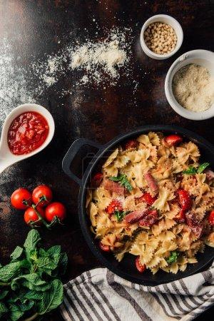 Foto de Vista desde arriba de pasta con jamón, piñones, salsa, tomates cherry, hojas de menta cubiertos de queso parmesano rallado en pan rodeado de ingredientes y toalla de cocina en mesa - Imagen libre de derechos