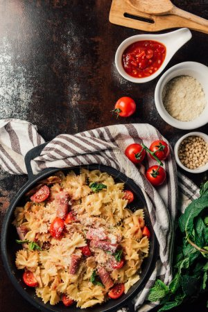 Photo for Top view of pasta with jamon, pine nuts, sauce, cherry tomatoes, mint leaves covered by grated parmesan in pan surrounded by ingredients and kitchen towel on table - Royalty Free Image
