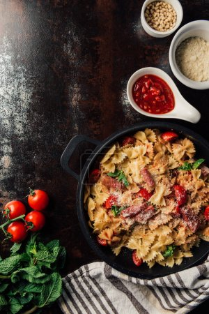 elevated view of pasta with jamon, pine nuts, sauce, cherry tomatoes, mint leaves covered by grated parmesan in pan surrounded by ingredients and kitchen towel on table