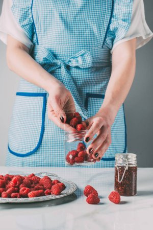 cropped image of woman in apron doing jam from raspberries over table