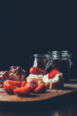 close up of sandwiches with cream cheese, strawberry slices and fruit jam on cutting board on black