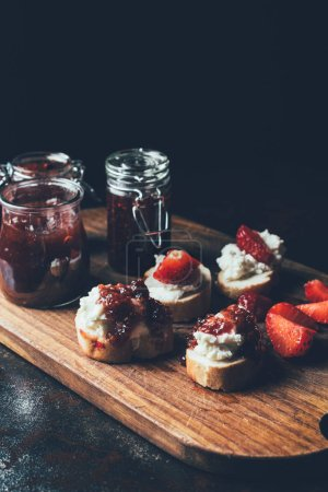 close up shot of jars with jam, sandwiches with cream cheese, strawberry slices and fruit jam on cutting board on black
