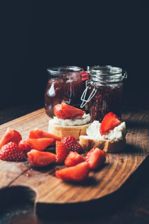 selective focus of sandwiches with cream cheese, strawberry slices and fruit jam on cutting board on black
