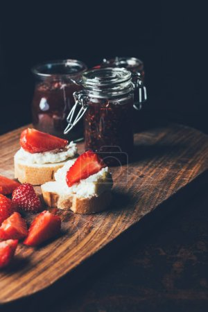selective focus of fruit jam in different jars, sandwiches with cream cheese, strawberry slices and fruit jam on cutting board on black