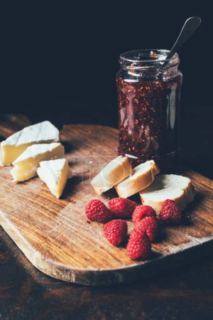 selective focus of brie, raspberries, jam in jar and baguette on cutting board at table