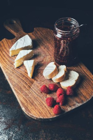 elevated view of brie, raspberries, jam in jar and baguette on cutting board at table