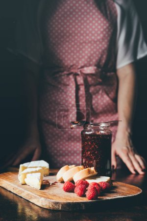 cropped image of woman in apron standing near table with brie, baguette slices, raspberries and jar of jam on cutting board