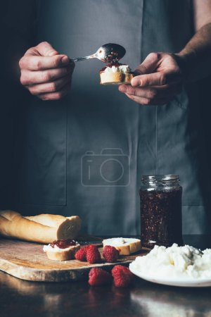 partial view of man in apron spreading strawberry jam on baguette with cream cheese