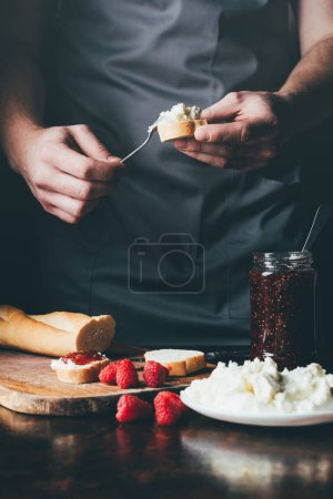 cropped image of man in apron spreading cream cheese on baguette over table with fruit jam