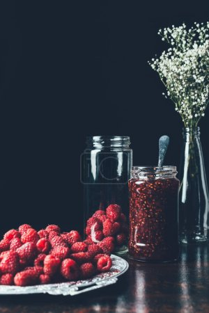 close up view of raspberries in silver tray, flowers, jar with jam on black