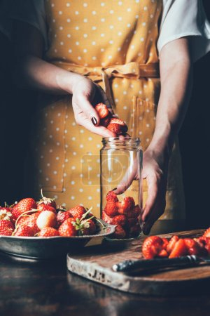 partial view of woman in apron standing at table and putting strawberries in jar