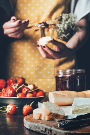 cropped image of woman in apron spreading strawberry jam on baguette