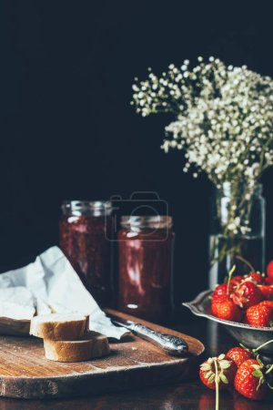 Close up view of strawberries with jam in jars and flowers on black