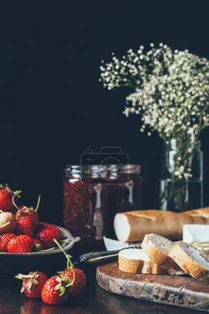 close up view of strawberries, baguette, jam in jars and flowers on black