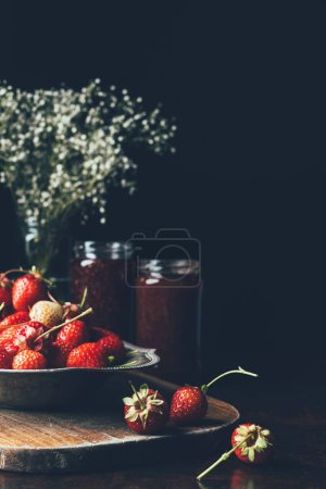 selective focus of strawberries in silver tray, flowers and jam in jars on black