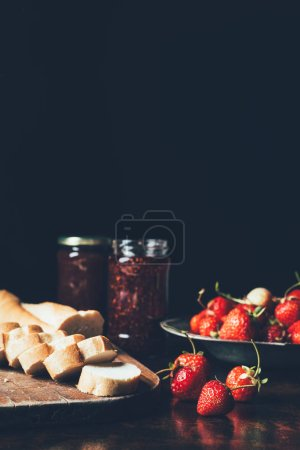 close up view of strawberries in silver tray, flowers and jam in jars on black