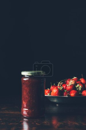 Photo for Selective focus of jar with strawberry jam and silver tray with strawberries on black - Royalty Free Image