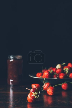 selective focus of strawberries in silver tray and fruit jam in jar on black