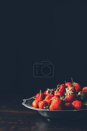selective focus of pile of strawberries in silver tray on black