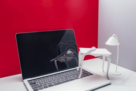 real size laptop with toy table and lamp in miniature red room