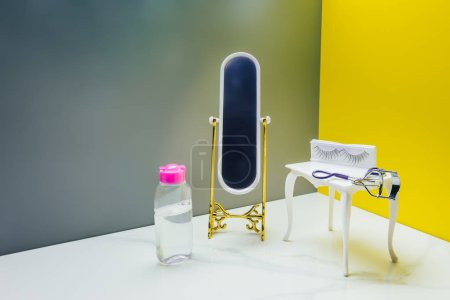 toy mirror and dressing table with bottle of lotion and eyelash curler in miniature room