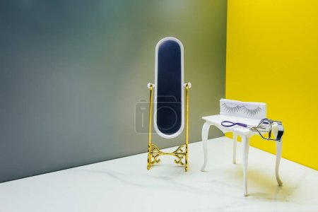 Photo for Toy mirror and dressing table with eyelash curler in miniature room - Royalty Free Image