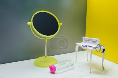Photo for Makeup mirror and dressing table with bottle of lotion and eyelash curler in miniature room - Royalty Free Image