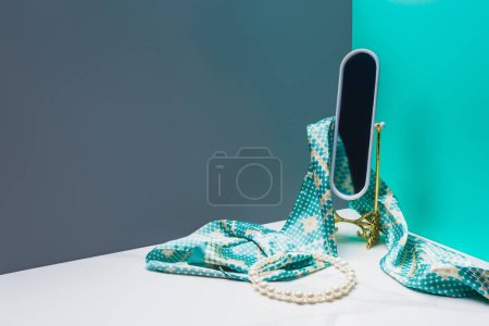 toy mirror with silk scarf and pearl necklace in miniature blue room