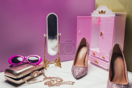 toy wardrobe and mirror with female accessories in miniature pink room