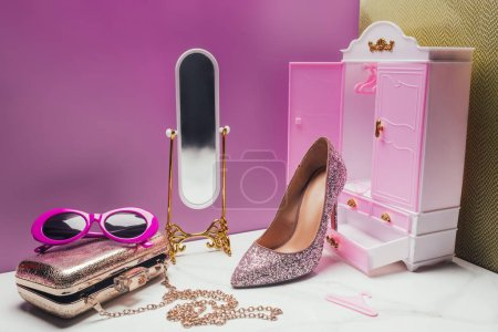 toy wardrobe and mirror with real size various female accessories in miniature pink room