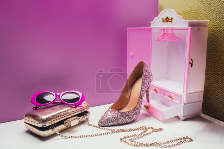 toy wardrobe with real size stylish female accessories in miniature pink room