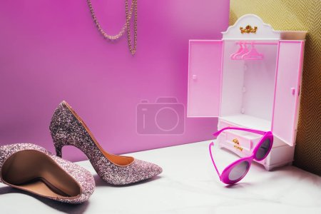 Photo for Toy wardrobe with real size high heels and vintage sunglasses in miniature pink room - Royalty Free Image