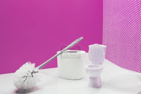 toy toilet with real size toilet brush and paper roll in miniature pink room