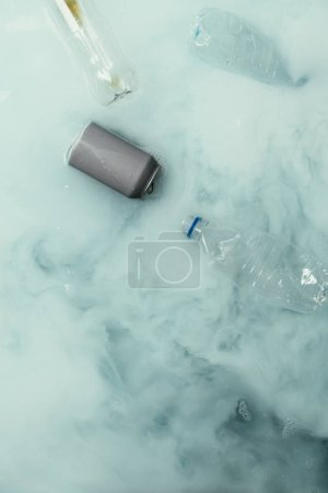 top view of smoke, can and plastic bottles flowing in water, environment protection concept